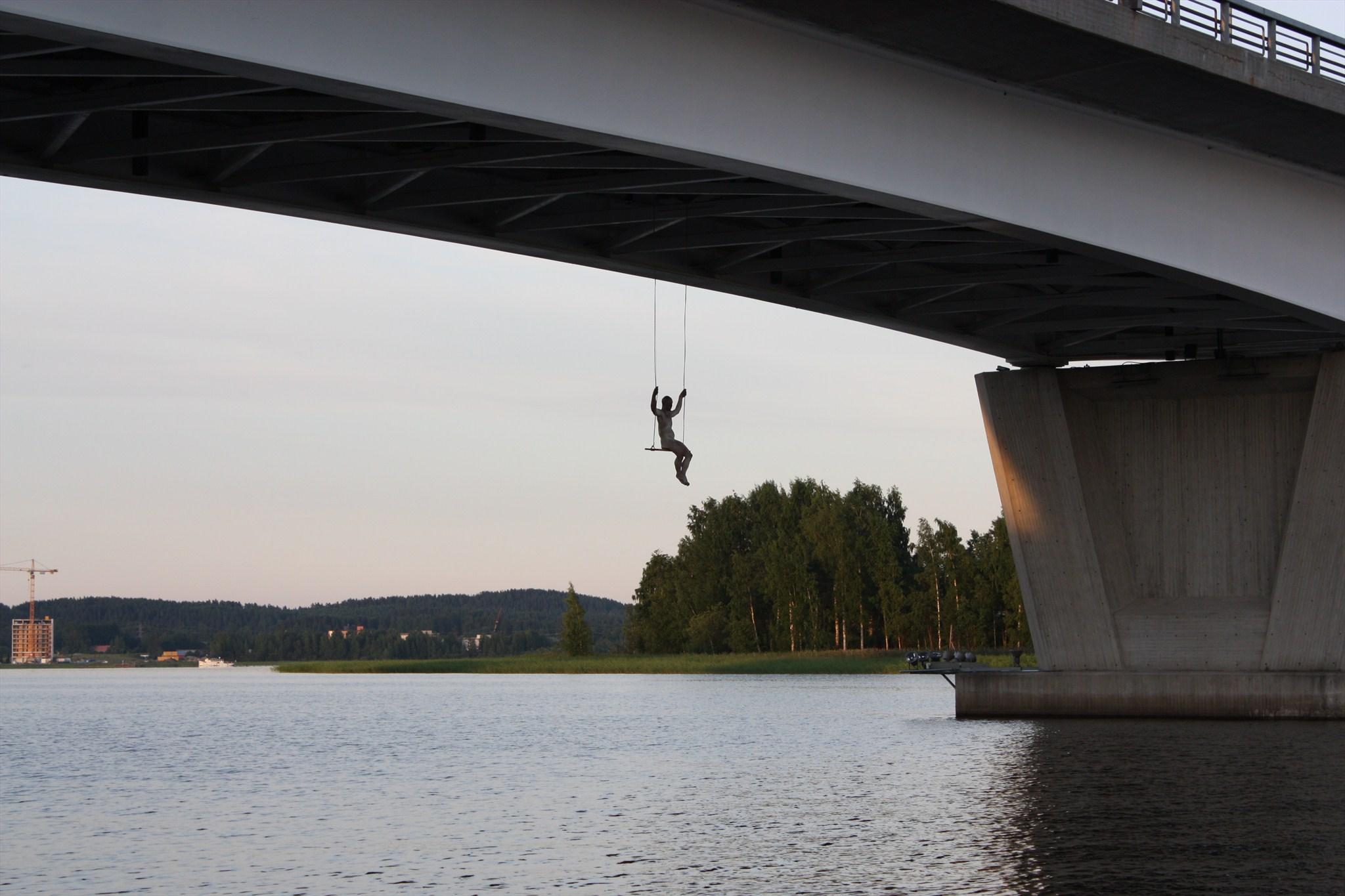 Kuva 1 - Keinuja kätkö esittelee sillalta roikkuvan patsaan. Kätkö on siis patsaan luona.