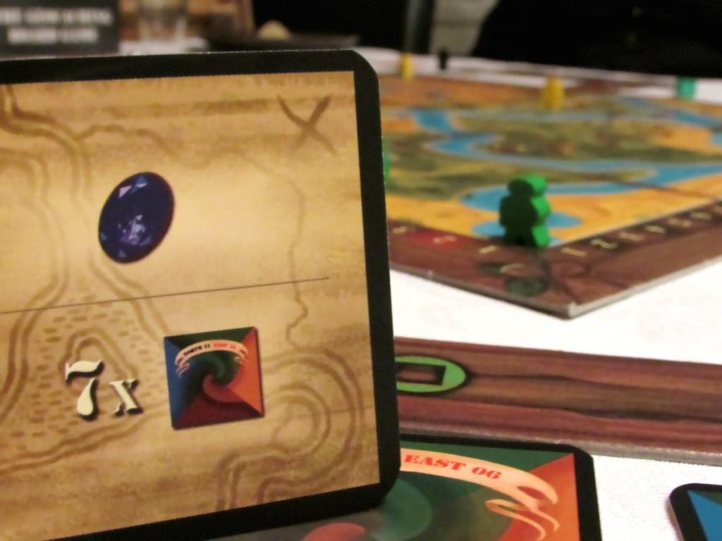 Kuva 5 - Tehtäväkortti kertoo pelaajan tavoitteen pelissä. Kuvan kortin tavoite on kerätä sininen jalokivi ja 7 geokätkömerkkiä.